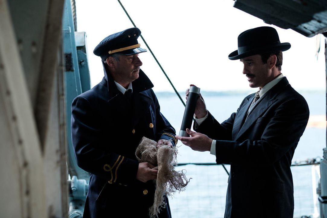 Tom Tunney (Craig McCarthy, r.) inspiziert die auf einem französischen Schiff gefunden Bombe und entdeckt, dass hinter den ganzen Explosionen im New... - Bildquelle: Darren Goldstein Cineflix 2015
