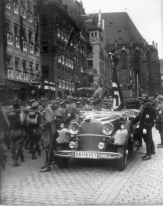 Diese Dokumentation geht der Frage nach, warum unterstützten Millionen Menschen Adolf Hitler (M., stehend) und seine Politik. Mit historischem Filmm... - Bildquelle: US National Archives