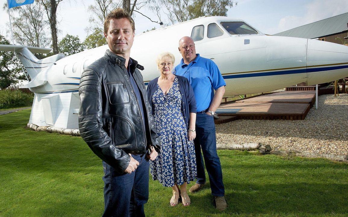 George Clarke (l.) trifft diese Woche Julia (M.) und Martyn Wiseman (r.). Das Ehepaar hat sich für 4.000 Pfund das Wrack eines extravaganten Privatj... - Bildquelle: Victor De Jesus UNP